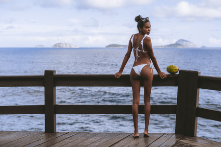 Rear view of a charming young black girl standing half-turned to the camera in the swimsuit on the observation point near the ocean with coconut next to her; copy space area on the left for a text