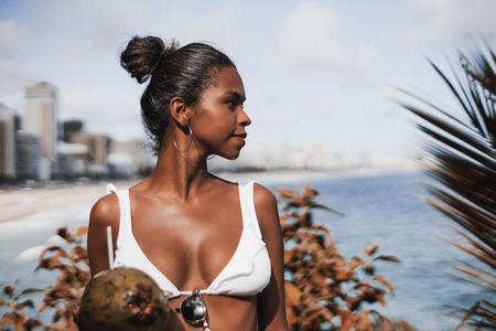 Young appealing African-American female in the swimming suit and with coconut in front of coastline looking aside; portrait of dazzling Brazilian girl in swimsuit and with coco near the beach of Rio