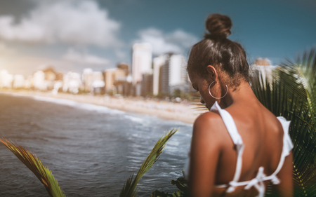 Rear tilt-shift view with selective focus of an African-American girl on a high point of an observation deck looking down on the cityscape, coastline, bay, and the beach below her in the distance