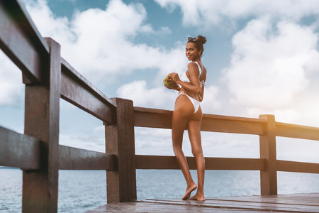 Cheerful sexy African-American girl in a white swimsuit half-turned to the camera, is standing on the wooden pier near the fence and drinking coconut water from a fresh coco; cloudscape behind her