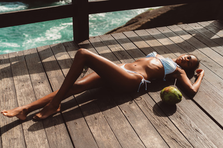 A svelte sexy African-American girl in the swimsuit is laying on a wooden surface of a pier and sunbathing, with coconut with straw near her; fence and ocean water in the background