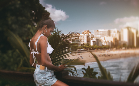 True tilt-shift shot of a young cute black girl checking just filmed photos on her smartphone while standing on the pier with the view on the city beach and the coastline, copy space area on the right