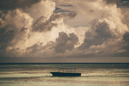 A lonely boat is lying at anchor in the open sea during the evening with a stunning cloudscape above on the sunset; an empty anchored blue vessel in the ocean not far from the coast, seascape behind