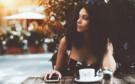 Charming young woman with curly hair is looking aside while sitting in a street cafe with the cup of delicious tea and a small metal teapot in front of her, holding hand on the smartphone on the table Banco de Imagens