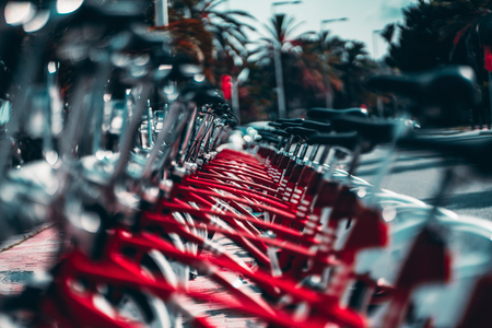 The row of parked bicycles for public use, vivid red colors with selective focus in the middle, shallow depth of field with strong bokeh, palms in the background, sunny summer day in Barcelona, Spain Banco de Imagens