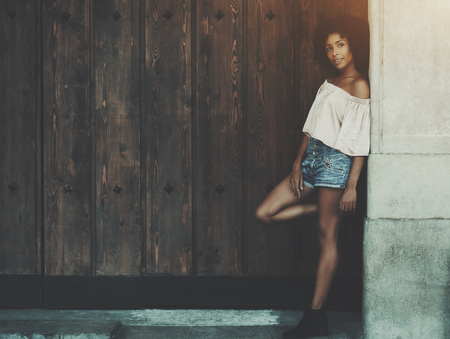 A beautiful curly African-American woman in jean shorts is leaning against a concrete street wall with huge wooden gates on the left and copy space place for a logo, your text message or advertising