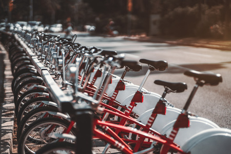 Close-up view with a shallow depth of field of the row of red rental bicycles plugged into their park parking place and stretching into the distance; strong bokeh, sunny day, Barcelona, Spain