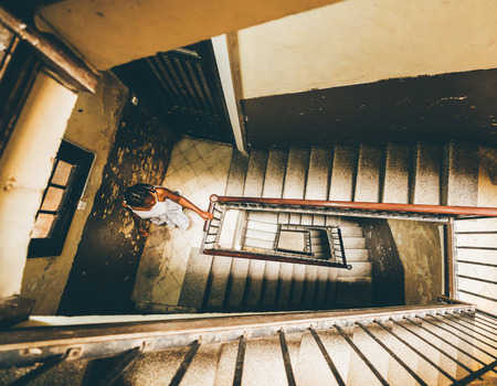 Wide-angle view of the black girl with braids in a white dress looking down the deep stairwell, while standing on the staircase which goes down by the spiral in an old house, preparing to descend