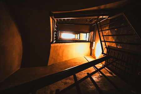 Wide-angle view from the bottom of a dark long stairwell going upwards in a spiral in an ancient building with a wooden door, yellow artificial lightning lamps, shadows, and bright window in the end Banco de Imagens