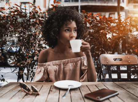 Beautiful African-American female is drinking delicious tea and looking aside while sitting in the street bar along and waiting for dessert; charming Brazilian lady drinking coffee in a cafe outdoors