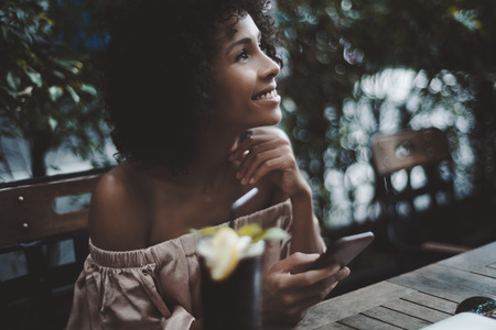 Portrait of dazzling African-American girl sitting in cafe and dreaming about something while holding the smartphone in hand; side view of curly black woman holding the cellphone in a bar outdoors Banco de Imagens
