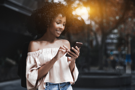 Charming cheerful African-American female with cellphone on a summer city street; cute Brazilian woman is smiling and typing a message while standing outdoors near a glass wall reflecting urban street