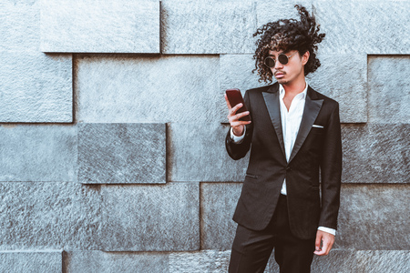 Curly stylish Asian guy in the sunglasses and in a formal suit is standing outdoors in front of textured street wall of blocks and typing a message on his smartphone while the wind ruffles his hair