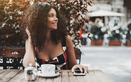 A young cute curly woman is smiling while sitting outdoors in a street bar with the cup of delicious tea and holding her hand on a smartphone; dazzling caucasian girl in street cafe looking aside