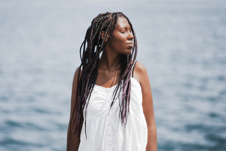 Portrait of a young charming black girl with braids, in a white dress, standing in front of a defocused seascape lit by sun, with closed eyes and with the head turned to the right