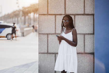 Beautiful African girl with braids, in sunglasses and white dress is standing near a concrete wall, on the city street in the shadow and checking her social network news using the smartphone