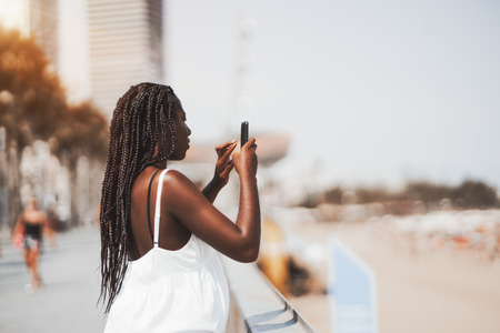 Cute black girl in a white dress is photographing sea and beach using the camera of her mobile phone; side view of a young African female with braids taking photos on the street via her smartphone
