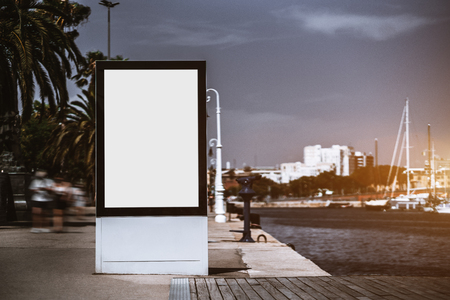 The billboard placeholder template on the city embankment, the sidewalk on the left; vertical blank advertising banner mock-up near quay; white empty informational signboard on the seafront