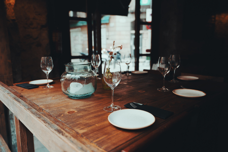 Table setting decor with cutlery, saucers, empty glasses, glass jar with a partially burnt candle inside, wooden table surface; dark interior of a street cafe or cozy restaurant, window behind