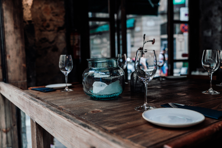Table setting decor with cutlery, saucers, empty glasses, glass jar with a partially burnt candle inside, wooden table surface; dark interior of a street cafe or cozy restaurant, entrance doors behind