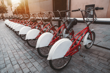 A long row of rental red parked bicycles on the pavement stone of Barcelona street; wide-angle view of the bikes plugged into their parking place and stretching into the distance on a sunny day, Spain 免版税图像