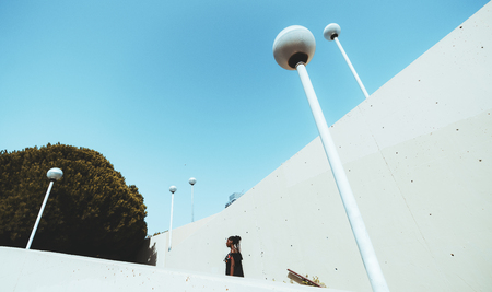 Wide-angle side view of a charming African girl with braids climbing a modern stairs with multiple streetlights on it and plenty of dots in concrete walls; the clear blue sky above, tree on the left