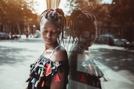 Charming young black female with braids is leaning against a glass wall and looking down on her shoulder; portrait of a cute African girl with braided hair, in dress near a huge window on the street
