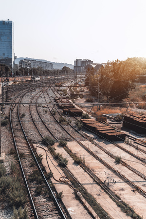 Wide-angle view from the top of several city railway tracks not far from a depot, with a lot of wires above, multiple heaps of wooden sleepers on the right, in Barcelona, Spain Banco de Imagens