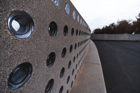 Wide-angle view with a shallow depth of field of a modern grainy concrete wall with seat place below, plenty of regular holes on the wall filled with round matte glass inserts, paved area on the right
