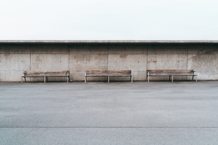 Wide-angle minimalist shot of three wooden benches with metal legs standing in front of a grunge concrete wall with small holes, a huge empty area of the asphalt with a single stripe in the foreground