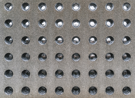 Modern concrete fence with glass insertions; a grainy texture of contemporary stone block with round holes inserts made of clean glossy partially transparent glass; the fragment of a concrete wall
