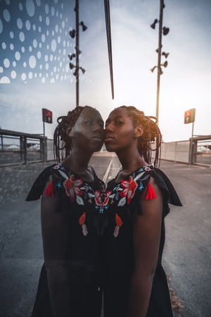 Vertical wide-angle shot of a charming black girl with braided hair, in dress, touching a glass wall with her face while standing outdoors; African girl with braids leaning against glass wall