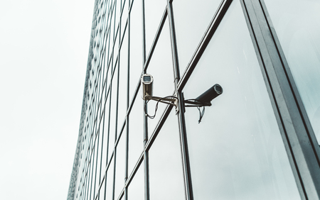 Close-up view of a contemporary surveillance video cam attached to the facade of a modern business skyscraper; security video camera on the frontage of an office high-rise