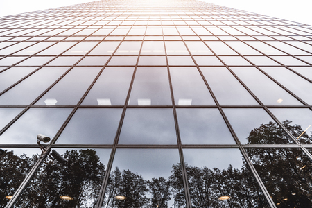 View from the bottom of a reflecting glass facade of a modern office skyscraper with flare on the top; a wide-angle shot of a business high-rise, laths of frontage stretching into the vanishing point