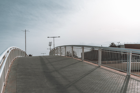 Empty bent pedestrian bridge with footpath: wide-angle shooting, evening clean sky with long shadows, pavement stone on the ground, poles and streetlights in the distance, Barcelona, Spain Banco de Imagens