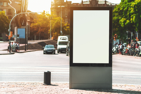 Outdoor empty informational board placeholder with a busy road behind; white blank city billboard mockup; vertical blank advertising banner template on the sidewalk with the road crossing behind Banco de Imagens