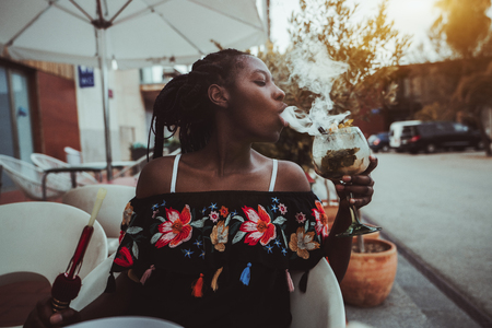 Portrait of a charming African girl sitting in a street cafe and making smoke in the glass of cocktail; young black female outdoors in a bar play with a hookah while drinking delicious mojito