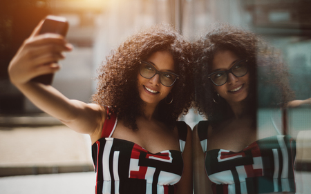 Dazzling hipster girl in eyeglasses and with bulky curly hair is taking a selfie using her smartphone while leaning agaianst the glass wall outdoors which fully reflects her and smiling