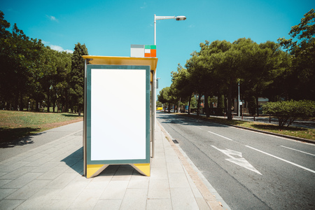 Empty billboard placeholder template on the city bus stop with the sidewalk on the left; blank advertising banner mock-up in urban settings; white empty informational signboard near the road