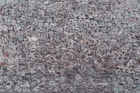 Wide-angle shot of the texture of the wall where broken bricks mixed with stones of different sizes, concrete, and cement layers