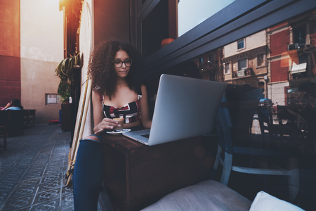 Cute young female entrepreneur with curly afro hair and in eyeglasses is sitting in an outdoor bar holding a cup of delicious cappuccino and using her laptop to finish her projects while coffee break