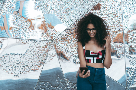 Young cheerful caucasian woman with curly afro hair and in eyeglasses is standing near a chrome metal perforated wall with multiple reflections and using her smartphone; a copy space area on the left