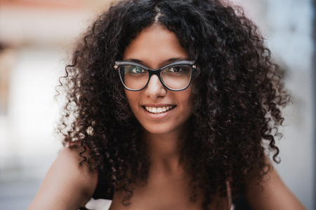 Close-up outdoor portrait of a dazzling young caucasian woman with curly bulky hair, brown eyes and in eyeglasses, she is smiling and looking at the camera, shallow depth of field