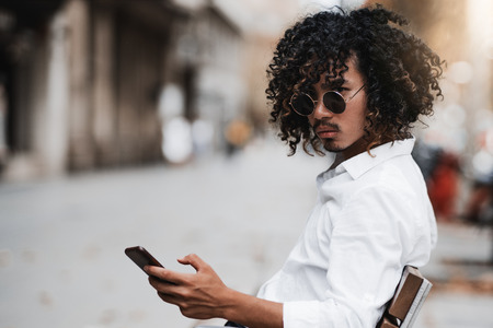 A serious stylish Asian guy with curly hair and in sunglasses is sitting on the bench near a sidewalk and looking aside while typing a message via his smartphone, with a copy space area on the left Stock fotó