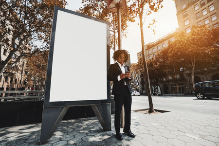 A young curly Asian man entrepreneur is using his cell phone outdoors next to the mock-up of a blank white urban banner; the businessman in a formal suit and sunglasses near a blank billboard template Stock Photo