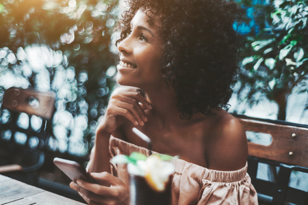 A dreamy African-American girl with curly afro hair is thinking about something happy and looking up after receiving a message from her boyfriend while sitting in the street cafe with her smartphone