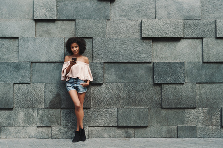 A beautiful cheerful African-American woman with a medium curly Afro hair is leaning against the wall on stony blocks and checking her phone with a copy space area on the right for your ad text