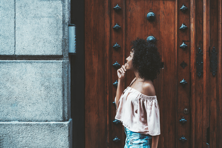A side view of a beautiful African American girl is contemplating an apartment number before using an outdoor intercom, with a huge antique wooden door with ironwork behind her Stock Photo