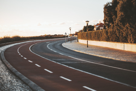 The view of an empty tidy two-way road making a turn to the right, with road marking, bicycle lane, lanterns, and sidewalks made of pavement stone, shallow depth of field, evening in Cascais, Portugal