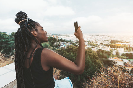 A cheerful cute African girl is photographing amazing evening cityscape from high above using her smartphone; young black female with braided hair using the cellphone to take pictures of a landscape 스톡 콘텐츠